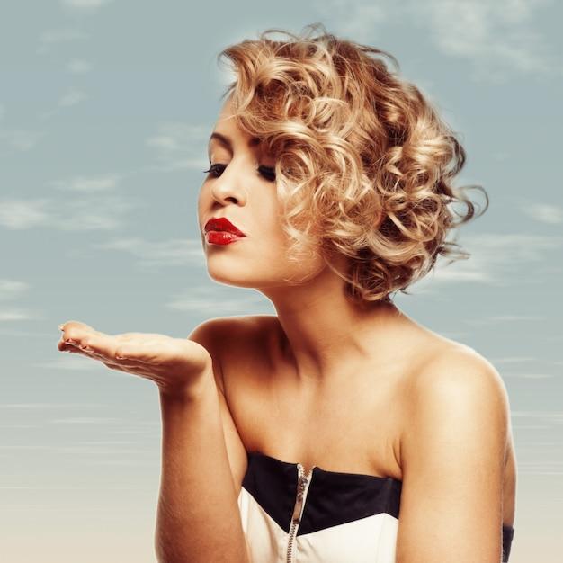 Junge schöne blonde frau, die zu ihrem valentinsgruß geküsst wird Premium Fotos