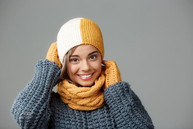 Junge schöne blonde frau im strickmützenpulloverschal und in den handschuhen, die auf grau lächeln. Kostenlose Fotos