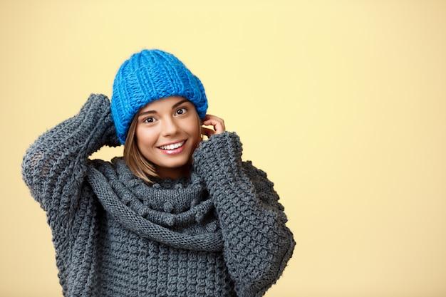 Junge schöne blonde frau in strickmütze und pullover lächelnd auf gelb. Kostenlose Fotos