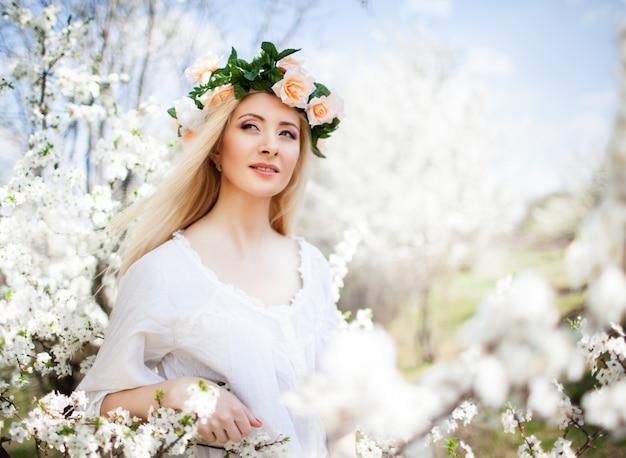 Junge schöne blonde lächelnde frau im weißen kleid und im rosenkranz Premium Fotos
