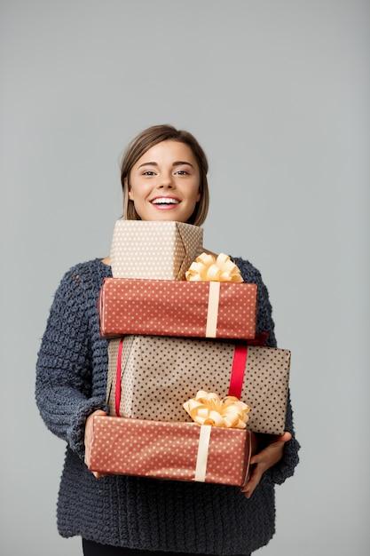 Junge schöne blondhaarige frau im gestrickten pullover lächelnd, die geschenkboxen auf grau hält. Kostenlose Fotos