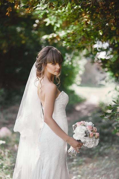 Junge schöne braut in einem eleganten kleid steht auf dem feld nahe dem wald und hält blumenstrauß von rosa blumen und von grüns mit band an der natur. draußen. nach der trauung. Premium Fotos