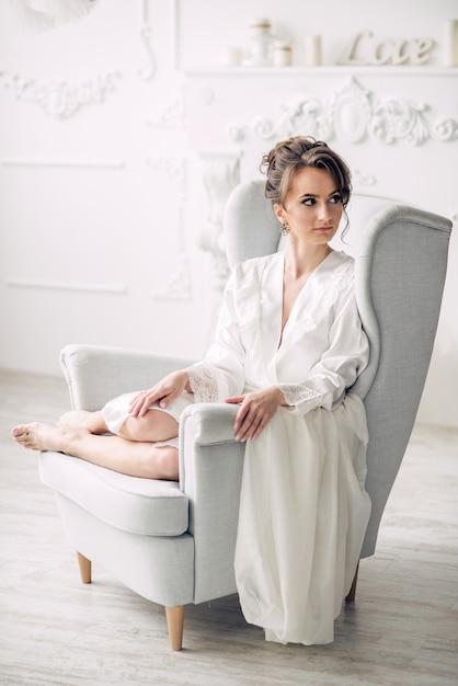 Junge schöne braut in einem weichen weißen gewand, das auf einem stuhl in einem hellen innenraum mit kerzen auf dem hintergrund sitzt Premium Fotos