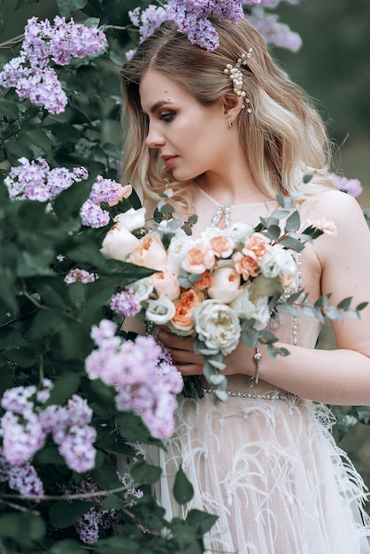 Junge schöne braut mit einem hochzeitsblumenstrauß nahe fliederbüschen Premium Fotos