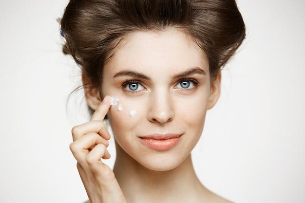 Junge schöne brünette frau in den lockenwicklern, die cremiges gesicht lächeln. gesichtsbehandlung. schönheitsgesundheit und kosmetologie. Kostenlose Fotos