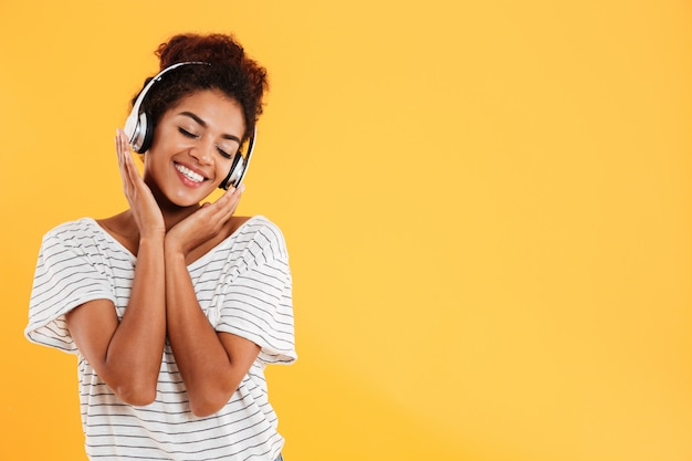 Junge schöne dame mit lockigem haar, das musik lokalisiert hört Kostenlose Fotos