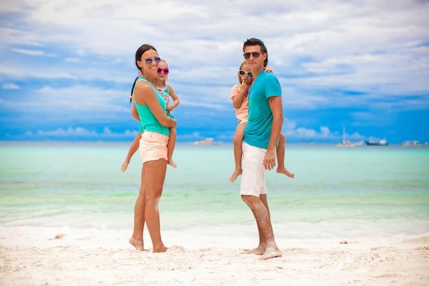 Junge schöne familie mit zwei kindern, die kamera auf tropischen ferien betrachten Premium Fotos