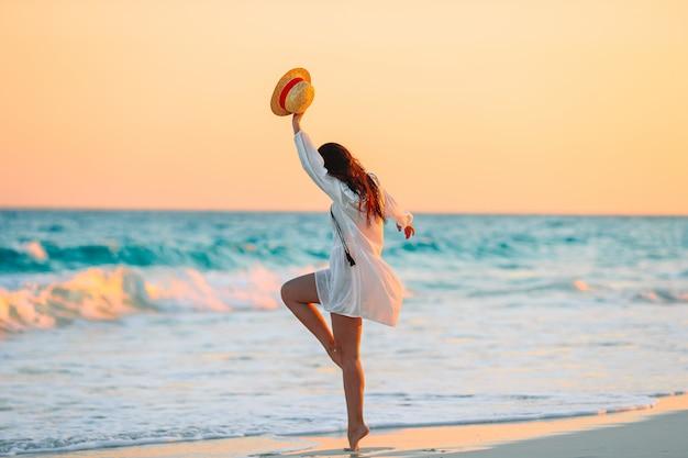 Junge schöne frau am tropischen strand im sonnenuntergang. Premium Fotos