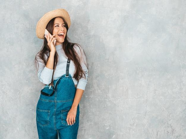 Junge schöne frau, die am telefon spricht. modisches mädchen in der zufälligen sommeroverallkleidung und -hut. Kostenlose Fotos