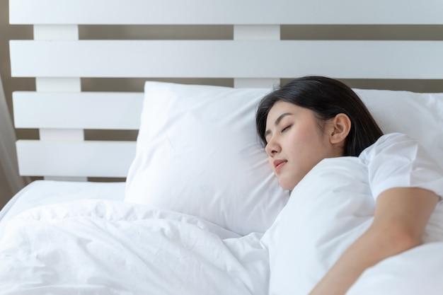 Junge schöne frau, die auf dem bett schläft Kostenlose Fotos