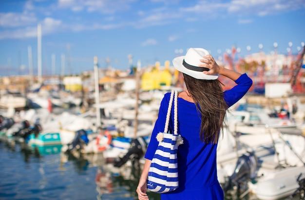 Junge schöne frau, die auf dock nahe dem boot am sonnigen tag sich entspannt Premium Fotos