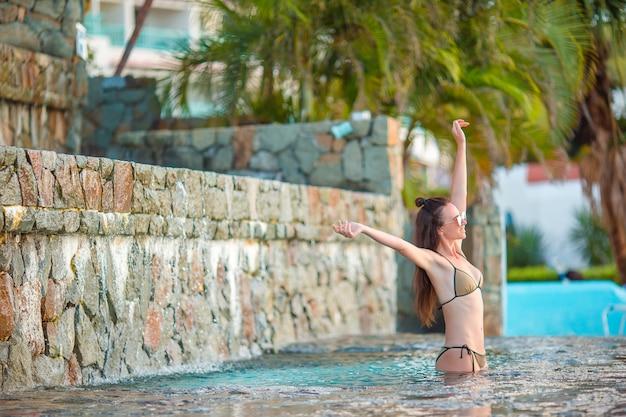 Junge schöne frau, die den luxuriösen ruhigen swimmingpool genießt. Premium Fotos