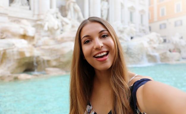 Junge schöne frau, die ein selfie am trevi-brunnen nimmt Premium Fotos