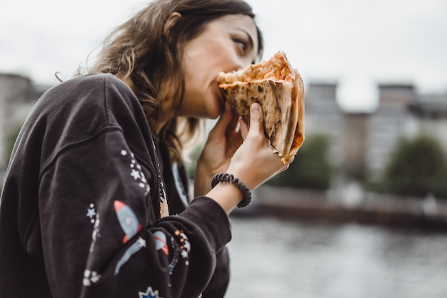 Junge schöne frau, die eine scheibe der pizza auf stadtstraße isst Kostenlose Fotos