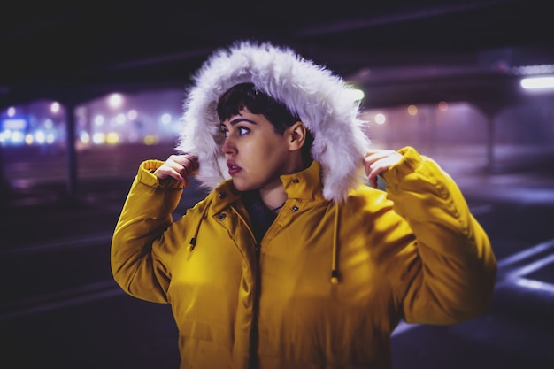 Junge schöne frau, die einen gelben wintermantel mit einer verschwommenen stadt in der nacht trägt Kostenlose Fotos