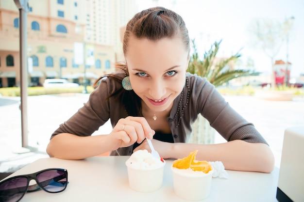 Junge schöne frau, die eiscreme isst Kostenlose Fotos