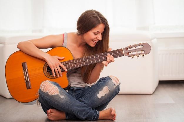 Junge schöne frau, die gitarre spielt Kostenlose Fotos