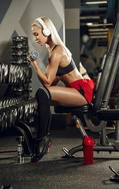 Junge schöne frau, die im fitnessstudio trainiert. konzept von fitness, training, sport, gesundheit Kostenlose Fotos