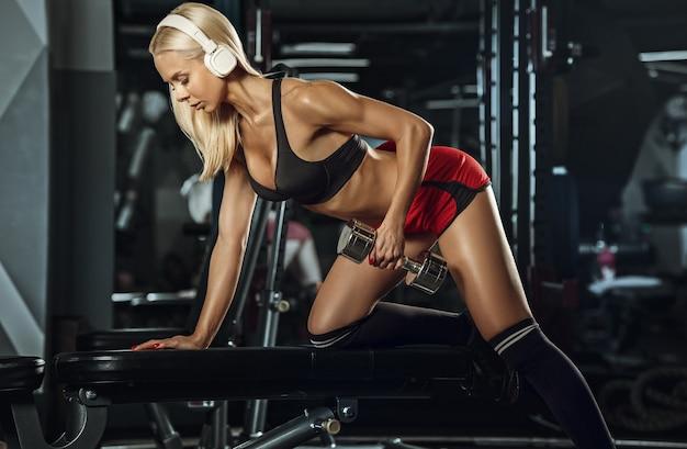 Junge schöne frau, die im fitnessstudio trainiert. Kostenlose Fotos