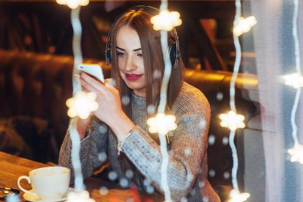Junge schöne frau, die im kaffee, trinkender kaffee sitzt. vorbildliches hören von musik. weihnachten, neujahr, valentinstag, winterferien Premium Fotos