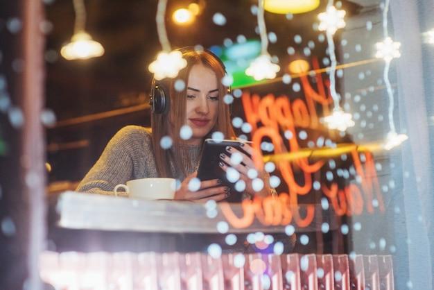 Junge schöne frau, die im kaffee, trinkender kaffee sitzt. vorbildliches hören von musik. Premium Fotos