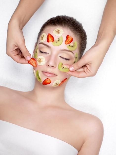 Junge schöne frau, die kosmetische fruchtgesichtsmaske von erdbeere, banane und kiwi am schönheitssalon erhält Kostenlose Fotos