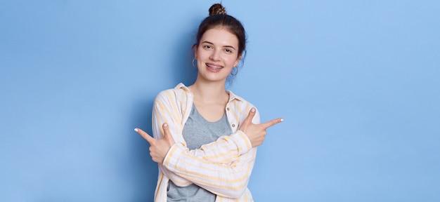 Junge schöne frau, die lässiges weißes hemd trägt, das lokal steht und mit beiden zeigefingern beiseite zeigt. Kostenlose Fotos