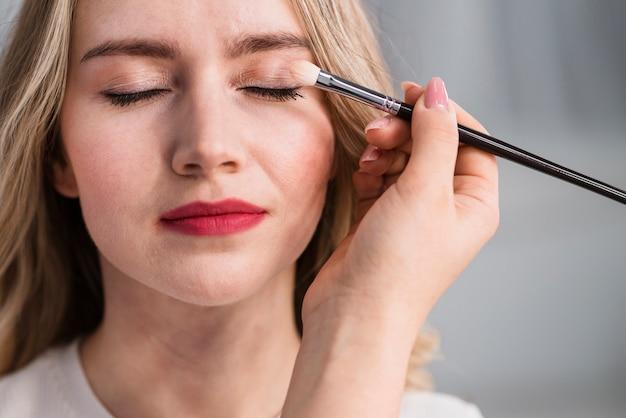 Junge schöne frau, die make-up durch bürste anwendet Kostenlose Fotos