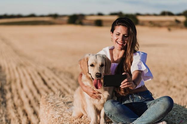 Junge schöne frau, die mit ihrem hund des goldenen apportierhunds auf einem gelben feld am sonnenuntergang geht Premium Fotos