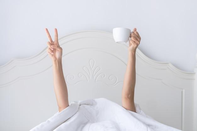 Junge schöne frau, die morgens im bett aufwacht, sich unter der decke versteckt, mit einer tasse kaffee die arme ausstreckt und das v-zeichen zeigt. Premium Fotos