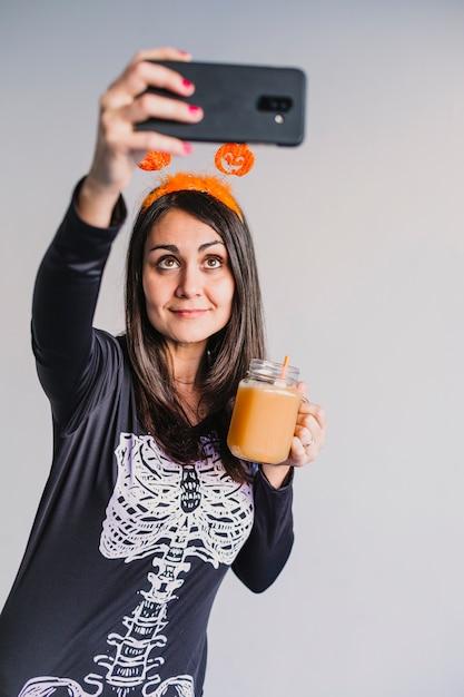 Junge schöne frau, die orangensaft trinkt und ein selfie mit handy nimmt. tragen eines schwarz-weißen skelettkostüms. halloween-konzept. drinnen Premium Fotos
