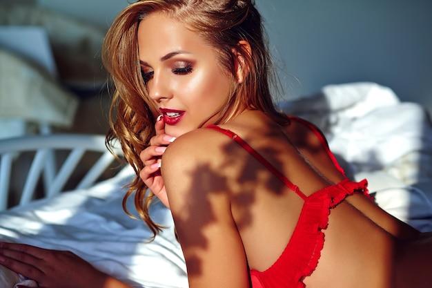 Junge schöne frau, die rote wäsche auf bett am morgen trägt Kostenlose Fotos