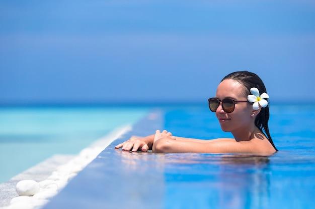 Junge schöne frau, die sommerferien im luxuxswimmingpool genießt Premium Fotos