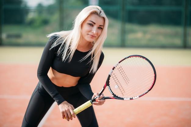 Junge schöne frau, die tennis auf einem gericht spielt. gesunder sportlebensstil Premium Fotos