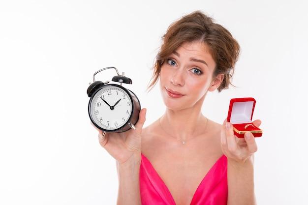 Junge schöne frau hält einen kasten für einen verlobungsring und einen wecker Premium Fotos