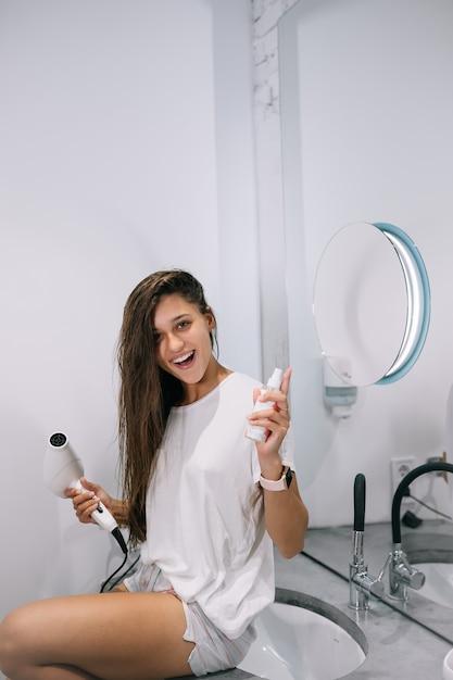 Junge schöne frau im badezimmer, die einen haartrockner und eine kleine flasche hält, nahe ansicht Kostenlose Fotos
