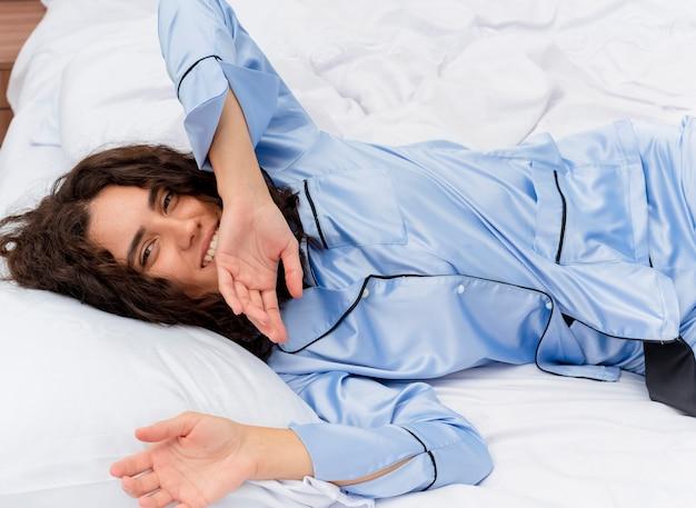 Junge schöne frau im blauen schlafanzug, der auf bett liegt, das auf weichen kissen glücklich und positiv ruht, die morgenzeit im schlafzimmerinnenraum auf hellem hintergrund genießen Kostenlose Fotos
