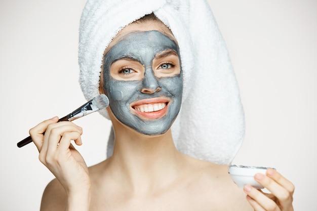 Junge schöne frau im handtuch auf kopfbedeckungsgesicht mit lächelnder maske. schönheitskosmetik und spa. Kostenlose Fotos