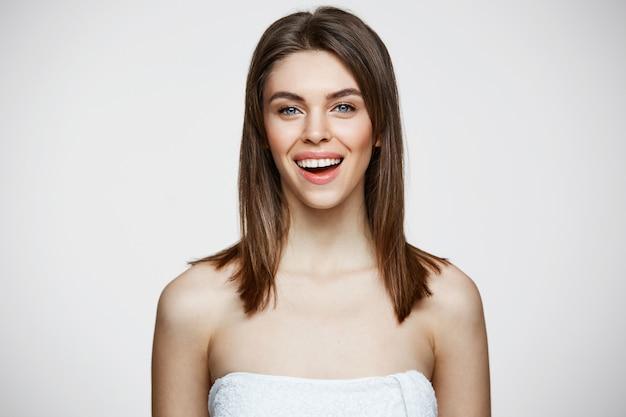 Junge schöne frau im handtuch mit natürlichem make-up lächelnd. kosmetologie und spa. gesichtsbehandlung. Kostenlose Fotos