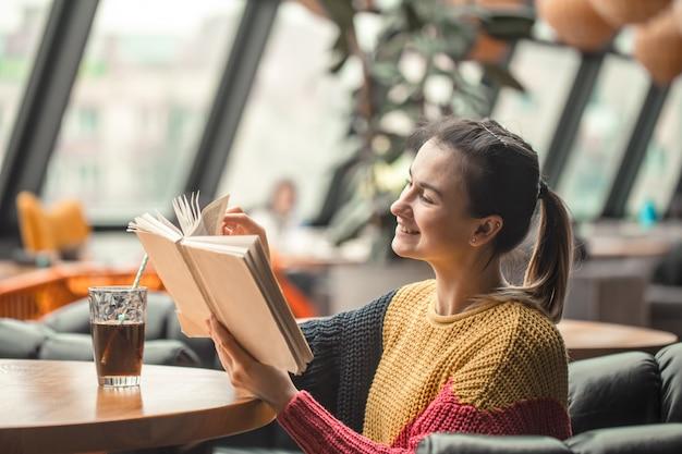Junge schöne frau im orangefarbenen pullover, der interessantes buch im café liest Kostenlose Fotos