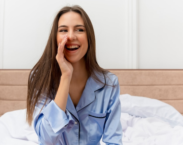 Junge schöne frau in den blauen pyjamas, die auf dem bett sitzen und mit der hand nahe mund glücklich und positiv im schlafzimmerinnenraum auf hellem hintergrund rufen oder schreien Kostenlose Fotos