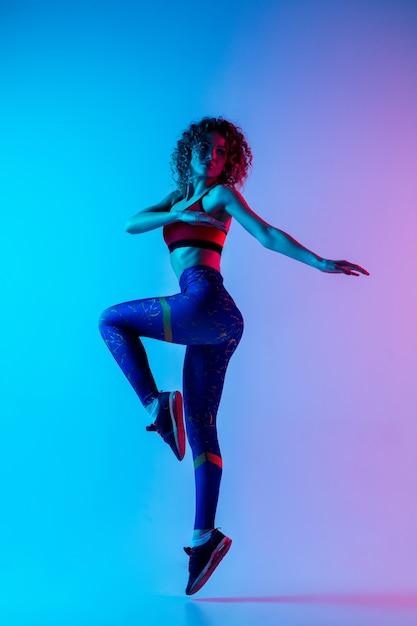 Junge schöne frau in der hellen sportbekleidung lokalisiert auf rosa-blauem hintergrund des gradienten im neonlicht. Kostenlose Fotos