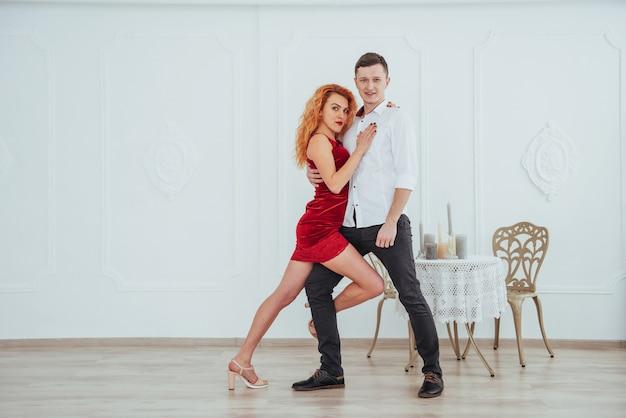 Junge schöne frau in einem roten kleid und in einem manntanzen getrennt auf einem weißen hintergrund. Premium Fotos