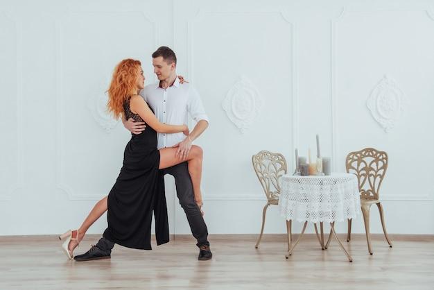 Junge schöne frau in einem schwarzen kleid und in einem mann im weißen hemdtanzen. Premium Fotos