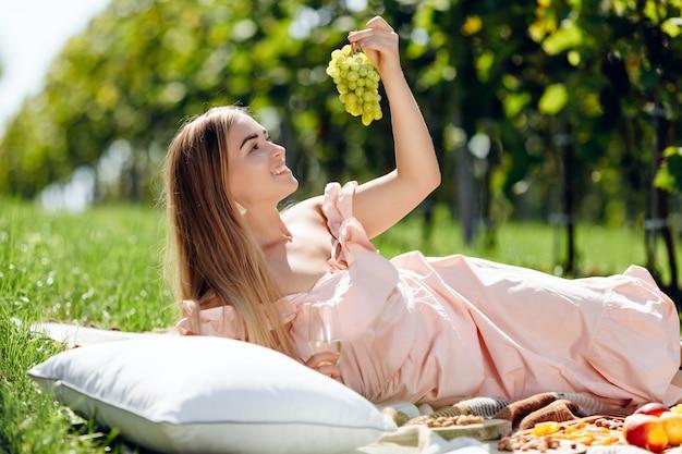 Junge schöne frau isst frische trauben in einem traubengarten Premium Fotos
