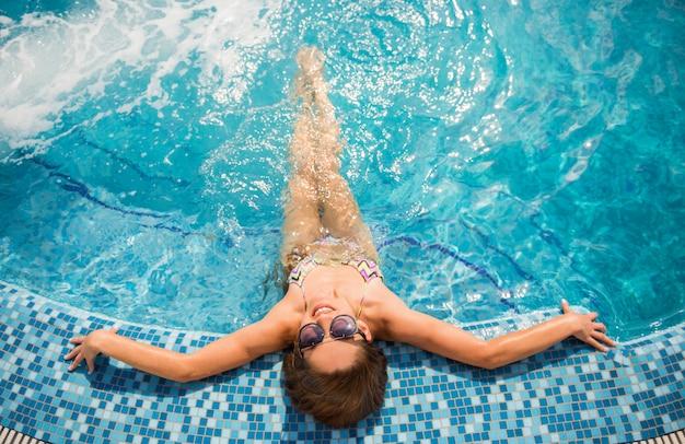 Junge schöne frau ist im swimmingpool entspannend. Premium Fotos