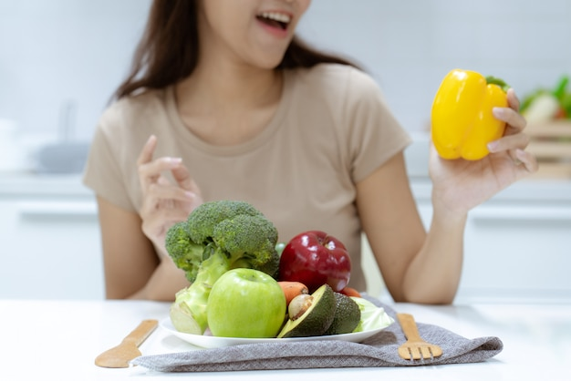 Junge schöne frau kümmern sich um ihre gesundheit, indem sie salat und frucht isst, anstatt fett und kalorien zu essen Premium Fotos