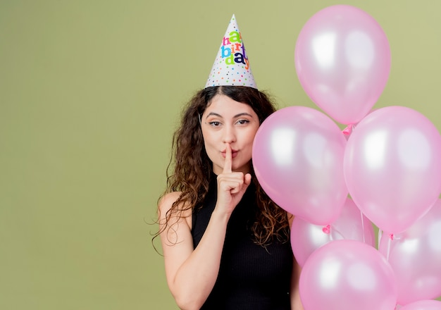 Junge schöne frau mit dem lockigen haar in einer feiertagskappe, die luftballons hält, die stille geste mit finger auf den lippen machen, die sicheres geburtstagsfeierkonzept stehen, das über lichtwand steht Kostenlose Fotos