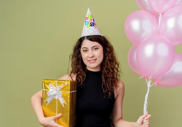 Junge schöne frau mit dem lockigen haar in einer feiertagskappe, die luftballons und geburtstagsgeschenk hält, die mit glücklichem gesicht über heller wand stehen Kostenlose Fotos