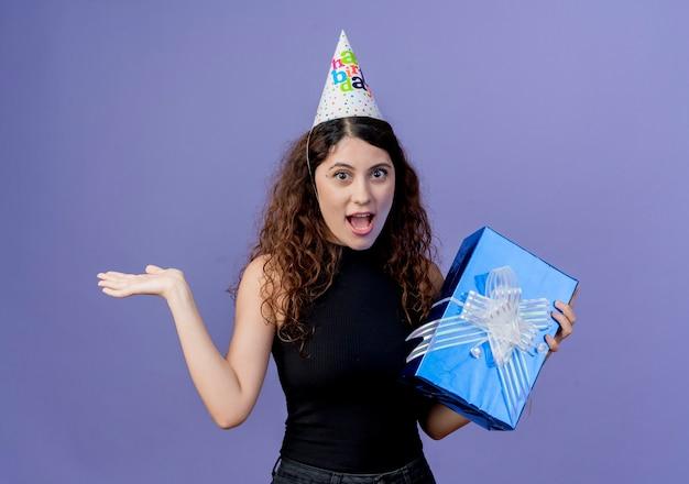 Junge schöne frau mit dem lockigen haar in einer feiertagsmütze, die geburtstagsgeschenkbox hält, die erstauntes und überraschtes geburtstagsfeierkonzept steht, das über blauer wand steht Kostenlose Fotos